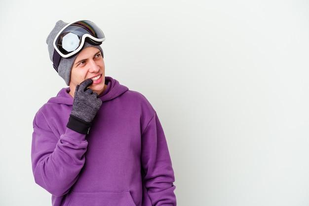 白い壁に隔離されたスノーボードボードを持っている若い男は、コピースペースを見ている何かについて考えてリラックスしました。