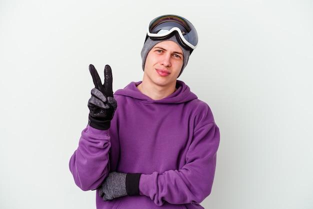指で2番目を示す白い壁に分離されたスノーボードボードを保持している若い男