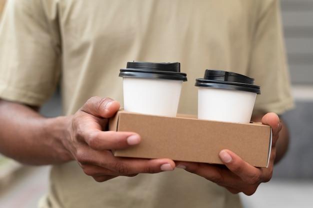 テイクアウトコーヒーを保持している若い男