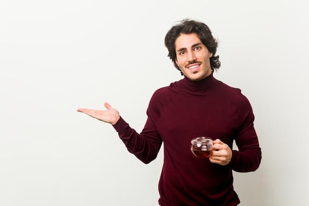 Молодой человек держа чашку чая показывая пустое пространство на ладони и держа другую руку на талии.