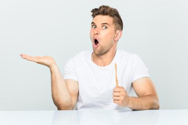 歯ブラシを持っている若い男は、手のひらにコピースペースを持っていることに感銘を受けました。