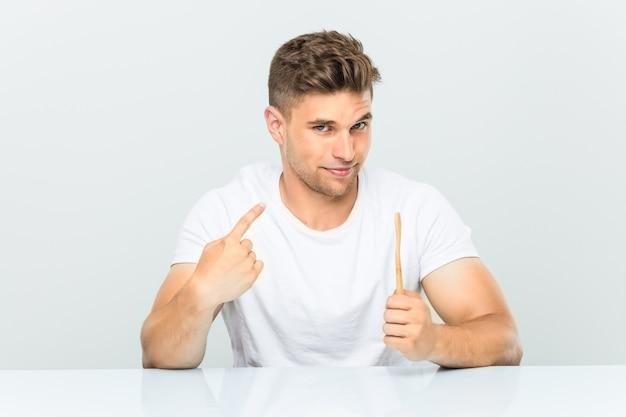 誘うように指で指さしている歯ブラシを持った青年が近づいてくる。