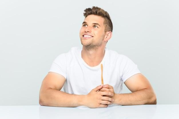 組んだ腕に自信を持って笑顔の歯ブラシを持って若い男。