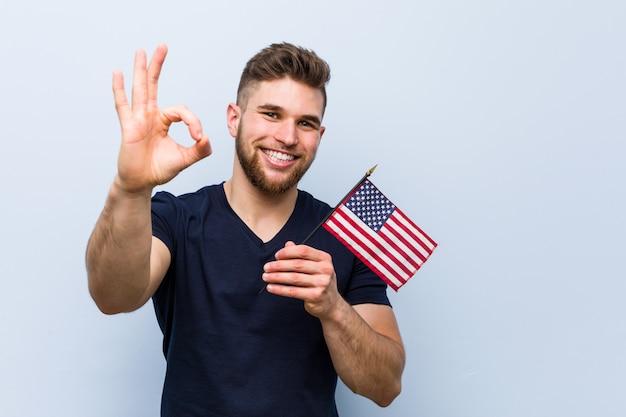 Молодой человек держит флаг сша, веселый и уверенный, показывая ок жест