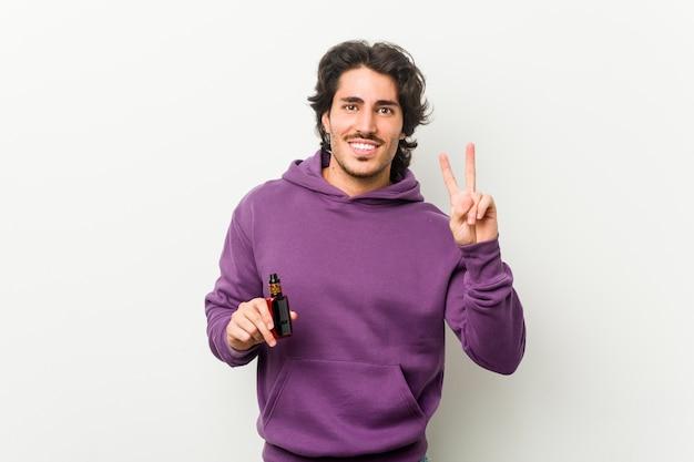 Молодой человек, держащий испаритель, показывая номер два пальцами.