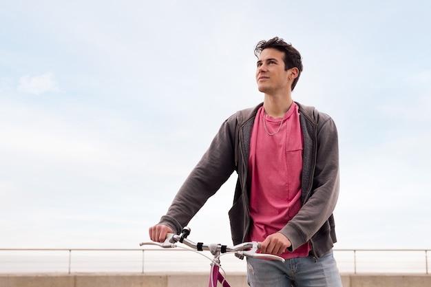 Молодой человек, держащий винтажный велосипед, концепция устойчивого транспорта и городского образа жизни