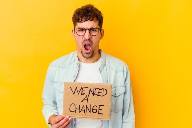 Молодой человек, держащий плакат с надписью `` нам нужно поменять '', кричит очень сердито и агрессивно