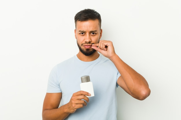 Young man holding an after shave cream with fingers on lips keeping a secret