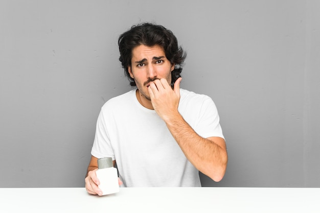 Young man holding an aftershave cream biting fingernails, nervous and very anxious.