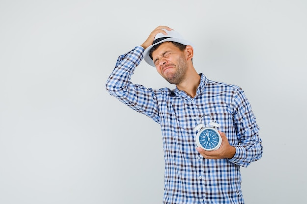 Young man holding alarm clock in checked shirt