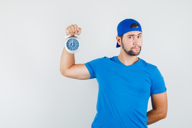 青いtシャツとキャップで目覚まし時計を保持し、物思いにふける若い男