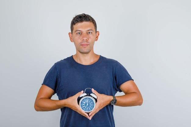 ダークブルーのtシャツに目覚まし時計を押しながら肯定的な若い男。正面図。