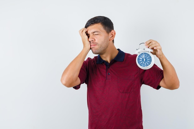 Tシャツに目覚まし時計を持って、忘れて見える若い男。正面図。