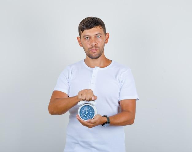 若い男が白いtシャツで目覚まし時計を保持し、時間厳守、正面を探しています。
