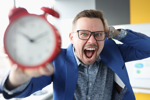 Young man holding alarm clock and shouting be in time