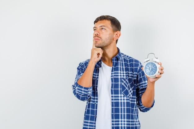 シャツの口の近くに指で目覚まし時計を保持し、物思いにふける若い男。正面図。