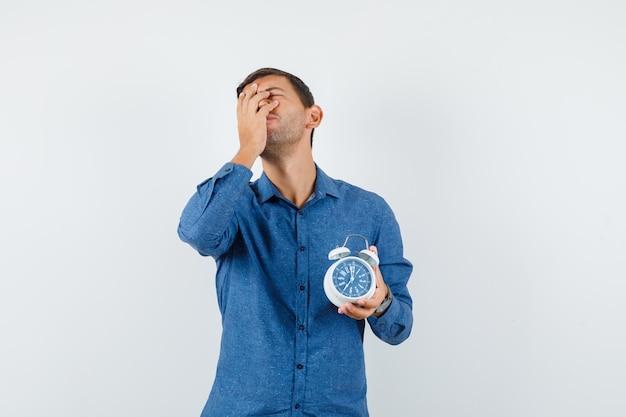 青いシャツを着た顔に手で目覚まし時計を保持し、忘れて、正面図を探している若い男。