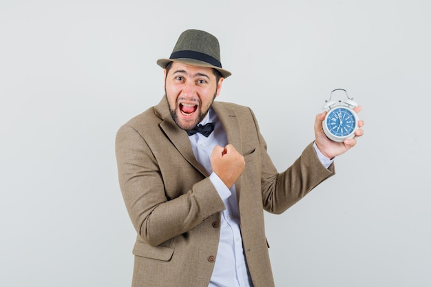Young man holding alarm clock with winner gesture in suit, hat and looking happy. front view.