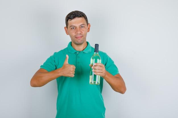 Молодой человек держит бутылку алкоголя и показывает большой палец вверх в зеленой футболке и выглядит довольным, вид спереди.