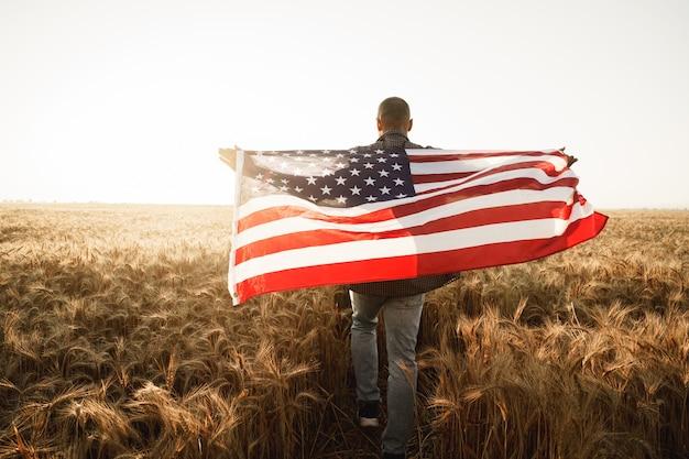 Молодой человек держит американский флаг на спине, стоя в пшеничном поле