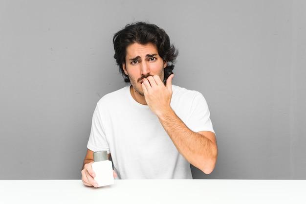 Молодой человек держит крем после бритья, кусая ногти, нервный и очень взволнованный.