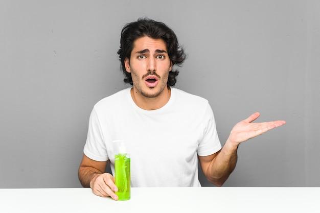 Молодой человек держа бутылку алоэ вера впечатленный держащ пустое пространство на ладони.