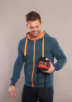 インスタントカメラを保持している若い男