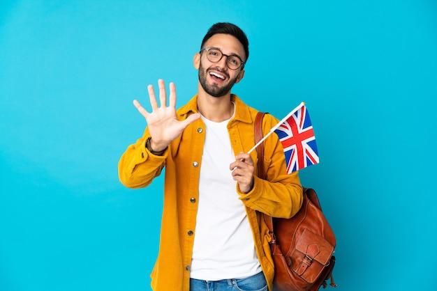 손가락으로 5 세 노란색 벽에 고립 된 영국 국기를 들고 젊은 남자