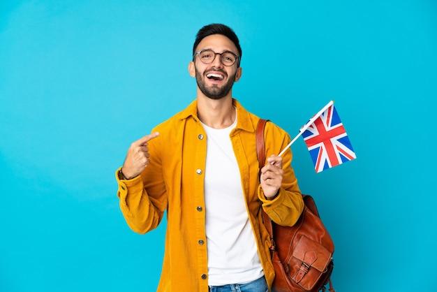 親指を立てるジェスチャーを与える黄色の壁に分離されたイギリスの旗を保持している若い男