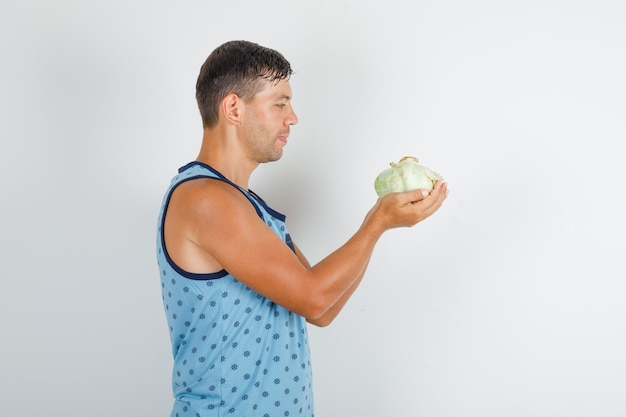 Молодой человек держит и смотрит на капусту в синем синглете.