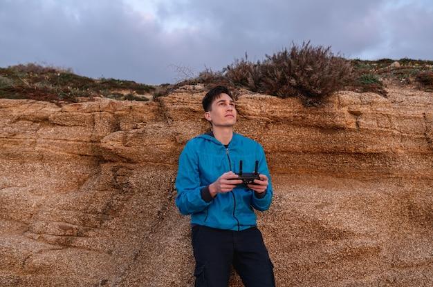 ドローンを飛ばしながら、集中した顔で上を見ているリモコンを持って使用している若い男