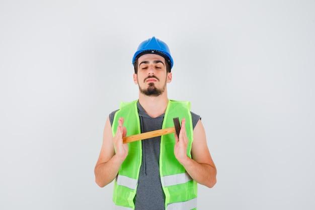 Молодой человек держит топор обеими руками и закрывает глаза в строительной форме и выглядит спокойным