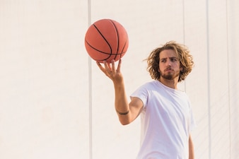 Young man holding basketball against wall