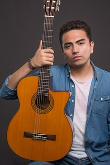 Young man holding a beautiful guitar on black background. high quality photo