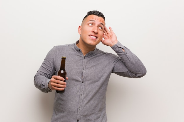 Young man holding a beer try to listening a gossip