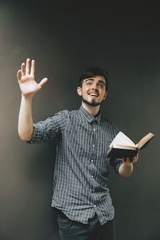 Young man holding a bible, student with  book