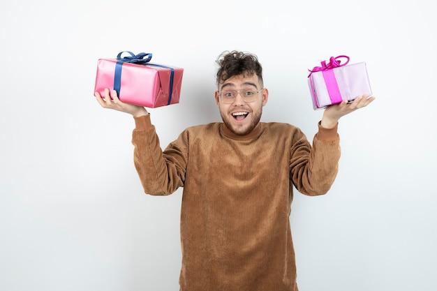 白い壁に大きなプレゼントギフトボックスを保持している若い男。