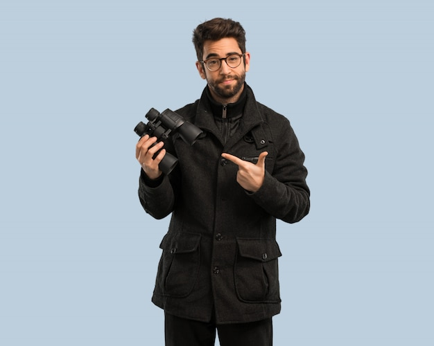Young man holding a binoculars