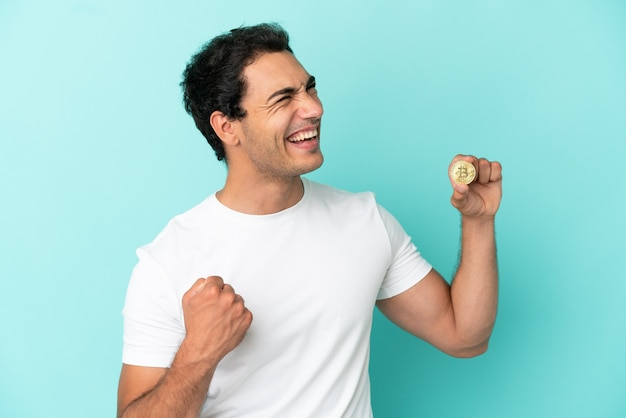 Young man holding a bitcoin over isolated blue background celebrating a victory