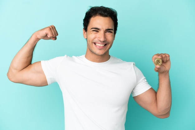 Young man holding a bitcoin over isolated blue background doing strong gesture