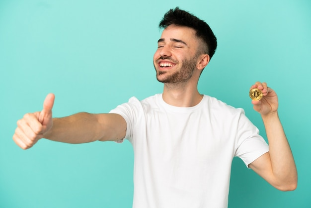 Young man holding a bitcoin isolated on blue background giving a thumbs up gesture