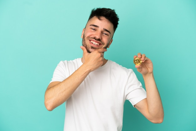 Young man holding a bitcoin isolated on blue background happy and smiling