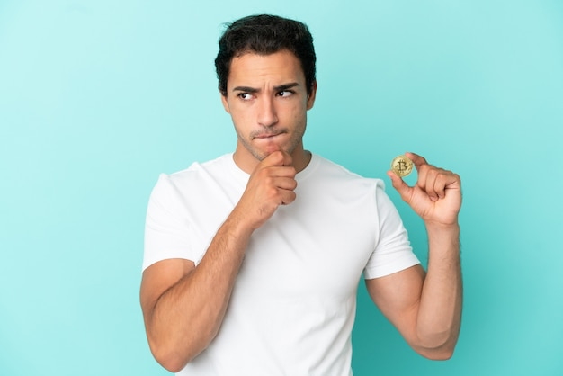 Young man holding a bitcoin over isolated blue background having doubts and thinking