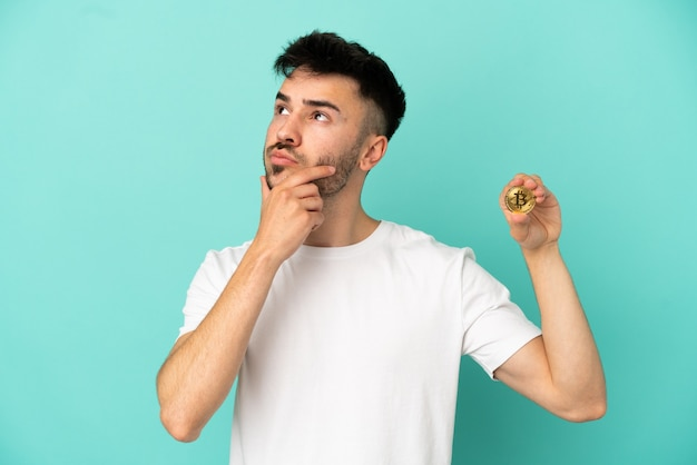 Young man holding a bitcoin isolated on blue background having doubts