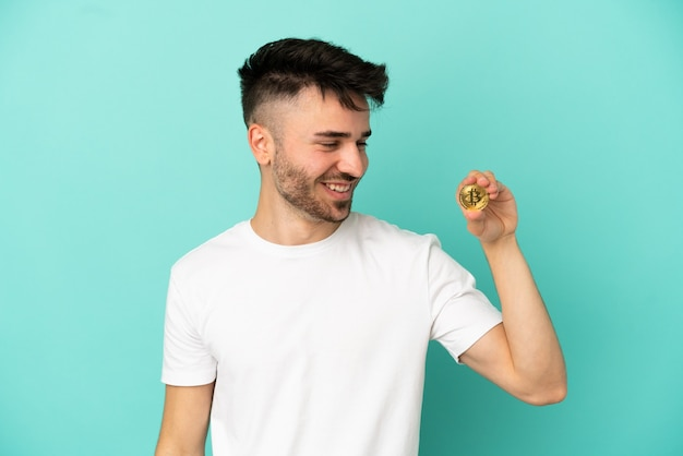 Young man holding a bitcoin isolated on blue background looking to the side and smiling