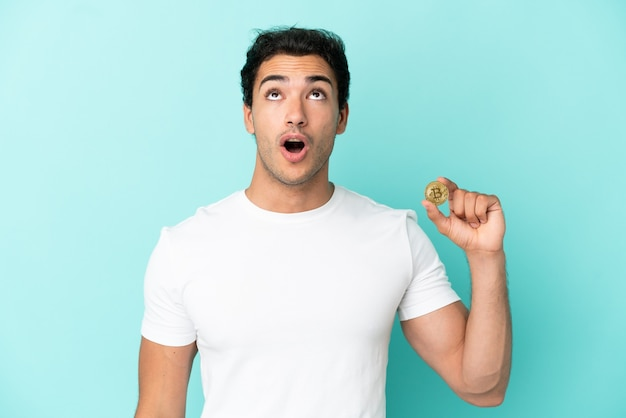 Young man holding a bitcoin over isolated blue background looking up and with surprised expression