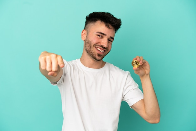 Young man holding a bitcoin isolated on blue background pointing front with happy expression
