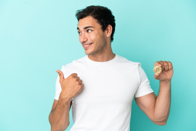 Young man holding a bitcoin over isolated blue background pointing to the side to present a product