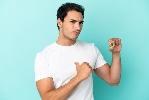 Young man holding a bitcoin over isolated blue background proud and self-satisfied