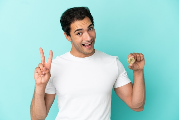 Young man holding a bitcoin over isolated blue background smiling and showing victory sign